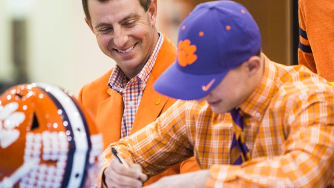 Dabo Swinney smiles as his son, wide receiver Will Swinney, signs with Clemson as a preferred walk-on on National Signing Day at D.W. Daniel High School on Wednesday, February 1, 2017 in Central.