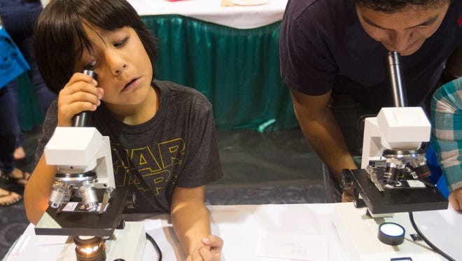 Mateo Barboza, 6, left, and his dad Juan look a cells under microscopes at the STEMtastic Day of Discovery on Saturday in Fort Myers.