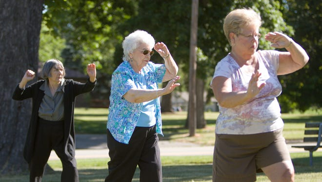 Participants (from left) Kathy McNabb, Micheline Flewelling and Barb Goodhue work through a movement in the Howell Senior Center's Tai Chi class. Normally held inside the senior center, the class conducted by instructor Paul Christensen was held on the front lawn as weather was too nice to stay inside.