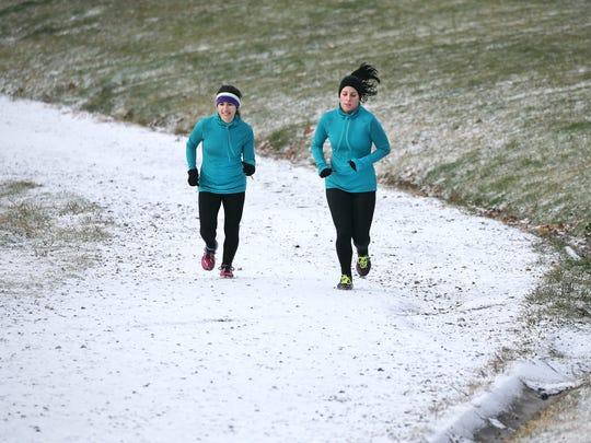 Kimberly Ball (L) and Kate Krysty of Rochester,  brave the snowfall to run the hill in Cobbs Hill Park near the reservoir as part of FIT1 exercise class.