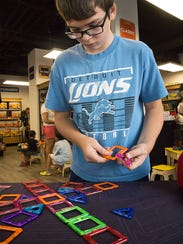 Daniel Etzel, 12, builds a pattern of Magformers parts.