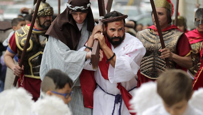 "Matt Plamann, portraying Simon of Cyrene, helps Ignacio León, portraying Jesus, with the weight of the cross at the Fifth Station of the Cross during St. Therese Catholic Church's ""Passion Play"" Friday in Appleton."