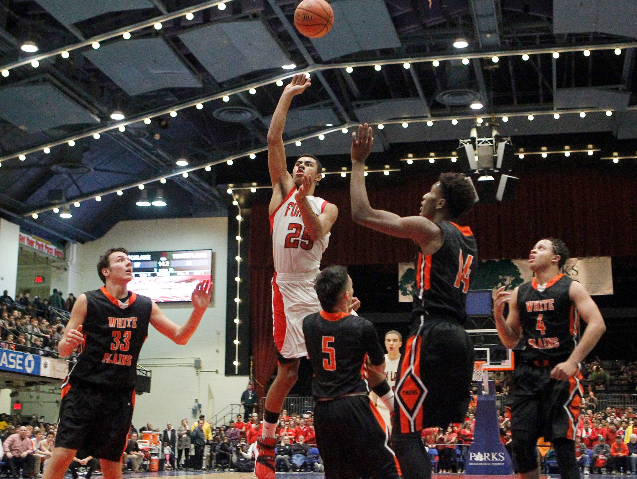 Fox Lane's Alex Olsen (25) drives past White Plains' Luis Cartagens (5) during the boys Class AA semi-final basketball game at the County Center in White Plains on Friday, February 26, 2016.