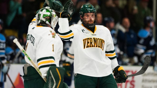 Catamounts forward Jake Fallon, right, and Catamounts goalie Mike Santaguida celebrate a goal during the Hockey East quarterfinal men's hockey game between the Maine Blackbears and the Vermont Catamounts at Gutterson Fieldhouse on Friday in Burlington.