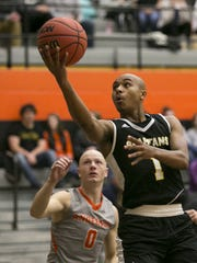 Adrian Johnson of Manchester University, puts a ball up as he is guarded by Trevor Lucas, during  the night's game against Manchester at Anderson University, Wednesday, Feb. 7, 2018. Alopecia is a medical condition that causes hair loss.