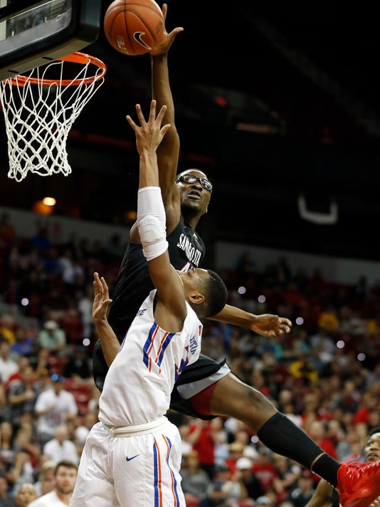 San Diego State's Valentine Izundu blocks a shot from Boise State's Paris Austin during the second half of an NCAA college basketball game in the Mountain West Conference tournament Thursday, March 9, 2017, in Las Vegas. San Diego State won 87-68. (AP Photo/Isaac Brekken)