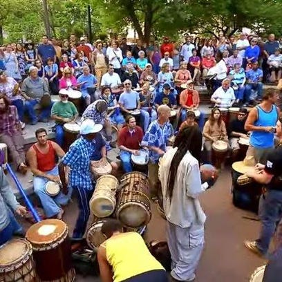 This still image from a video in the new Asheville branding campaign shows the weekly downtown drum circle in Pritchard Park.