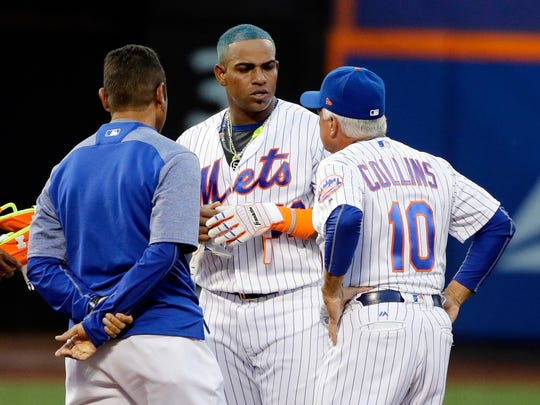 New York Mets' Yoenis Cespedes, center, talks to a trainer and manager Terry Collins (10) after hitting an RBI double during the second inning of the team's baseball game against the St. Louis Cardinals on Wednesday, July 19, 2017, in New York.