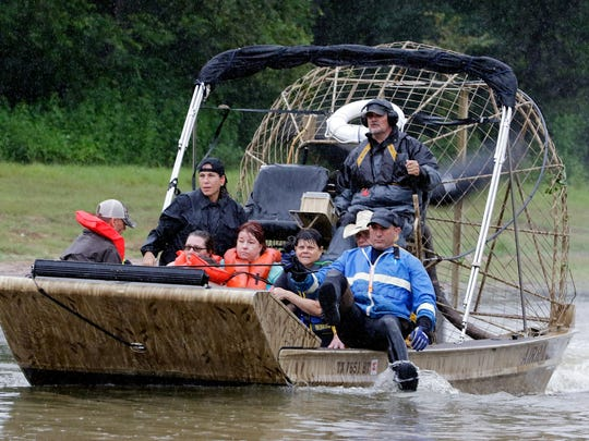 A boat ferries rescued residents from homes and apartments across the flooded area of Cypress Creek at Kuykendal 15 miles northwest of downtown Houston, Texas on Aug. 28, 2017.