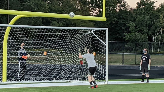 Gardner High boys' soccer assistant coach Christian Newton, left, throws a soccer ball over the football goal posts and the soccer goal while working through a drill with the Wildcats' goalies at the team's first practice, Friday evening, at Watkins Field in Gardner. Each goalie was tasked with catching the ball in the air before turning around and finding and stopping a shot sent on goal by assistant coach Angel Ruiz.