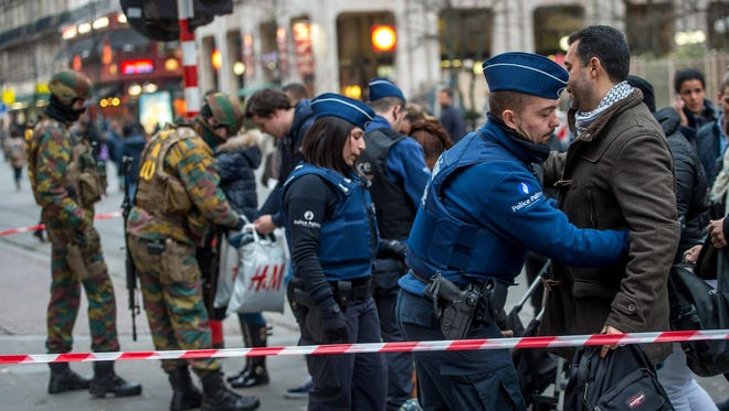 Police and soldiers carry out searches on people entering De Brouckere metro station in Brussels on March 24, 2016, two days after suicide attacks at Brussels airport and a metro station that left 31 people dead and 300 wounded.