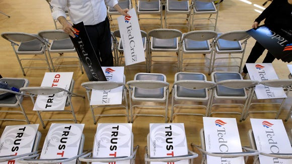 Volunteers place campaign signs on seats before a rally