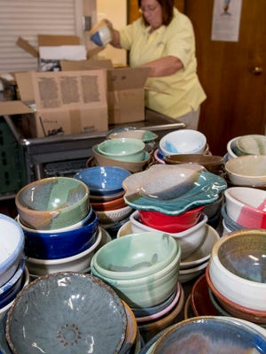 Lesa Andrada, with the Las Cruces Potter's Guild, helps unpack some of the more than 1,300 bowls Thursday afternoon at St. Paul's Methodist Church. The bowls will be available 11 a.m. Friday at the 25th Anniversary Empty Bowls fundraiser for the El Caldito Soup Kitchen. 10/19/17 Gary Mook/ for the Sun-News