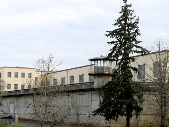 Tall concrete walls with guard towers surround the Oregon State Penitentiary, the state's only maximum-security prison, along State Street in Salem. Photographed on Wednesday, March 23, 2016.