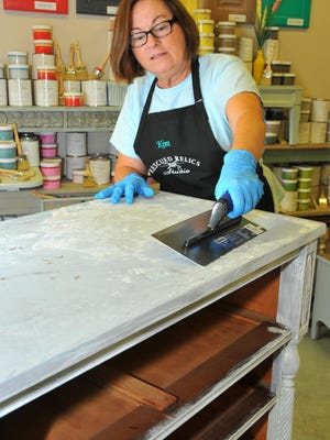 Kim Hunt, a former teacher at Space Coast Jr./Sr. High School, has quit teaching and opened Rescued Relics Studio in Rockledge, a DIY shop that helps people repurpose their furniture. The shop also sells supplies for chalk painting and finishes. She is applying Venetian plaster to a dresser she is working on.