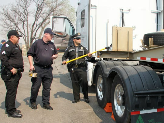 """New Mexico State Police Patrolman Darian Jarrott uses a """"hot dog"""" to check radiation levels on a truck used to transport radioactive waste during a drill Tuesday at the Carlsbad Point of Entry."""