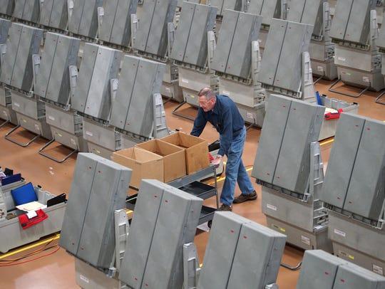 Technician Howard Hansel rolls equipment past voting