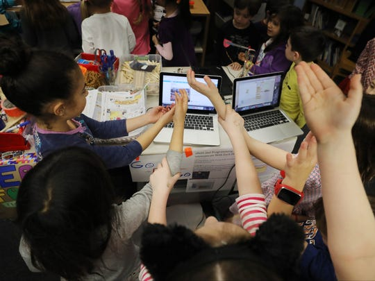 The first-graders raise their hands in the air as if they are tossing pizza dough because sensors use the uplifted hands and toss pizza that is on the computer screen.