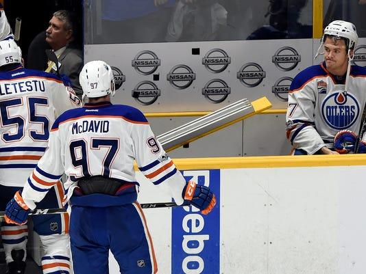 Edmonton Oilers defenseman Oscar Klefbom, right, of Sweden, waits on the bench as Mark Letestu (55) and Connor McDavid (97) leave the ice after Nashville Predators won 5-4 in an NHL hockey game Sunday, Feb. 26, 2017, in Nashville, Tenn. (AP Photo/Mark Zaleski)