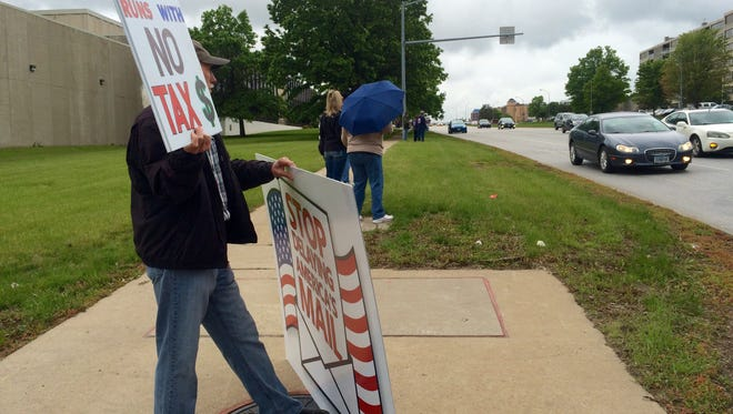American Postal Workers Union members stood outside the Des Moines U.S. Postal Service office Wednesday afternoon to voice their opposition to changes the United States Postal Service is undergoing.