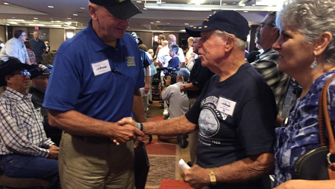 Lyle Umenhoffer (right) shakes hands with an attendee at the USS Indianapolis memorial service Sunday, July 26, 2015, at the Hyatt Regency in Downtown Indianapolis. Umenhoffer, 92, survived the attack that sank the U.S. Navy cruiser 70 years ago. He hopped a plane with his grandsons from California to Indianapolis for the reunion.