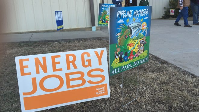 Pro and against signs welcome visitors to the Augusta County Expo to meet with Dominion representatives over their proposed natural gas pipeline Jan. 20, 2015.