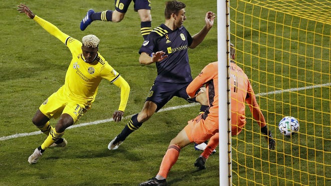 Columbus Crew SC forward Gyasi Zardes (11) scores a goal against Nashville SC defender Dave Romney (4) and Nashville SC goalkeeper Joe Willis (1) during the 2nd half of their MLS game at MAPFRE Stadium in Columbus, Ohio on September 19, 2020.