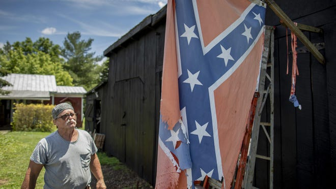 "Steve Lewis, 67, looks at his tattered Confederate battle flag hanging on the side of his barn in West Union, the Adams County seat. Lewis said he considers himself to be an anti-government ""rebel,"" and he said ""that flag sure looks like it's been through a battle."""