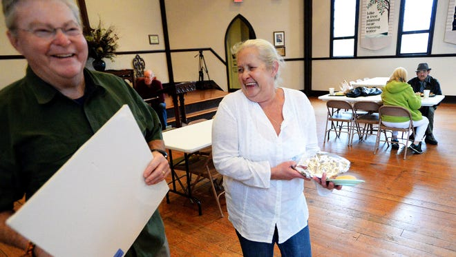 """Janet Wood, or the """"Queen,"""" shares a laugh Nov. 17 with one of the volunteers as she carries a lunch for her brother during Noon Lunch."""