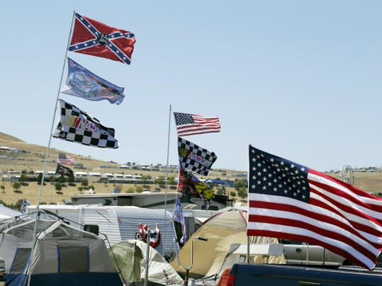 A number of flags, including a Confederate-themed one,  fly atop RVs in a campground outside the track during practice for the NASCAR Sprint Cup Series auto race Friday in Sonoma, California. NASCAR tracks have united to ask their fans to refrain from displaying the Confederate flag.