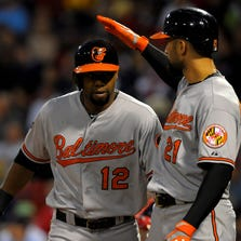 Sep 9, 2014; Boston, MA, USA; Baltimore Orioles right fielder Nick Markakis (21) congratulates left fielder Alejandro De Aza (12) after hitting a two run home run during the first inning against the Baltimore Orioles at Fenway Park. Mandatory Credit: Bob DeChiara-USA TODAY Sports