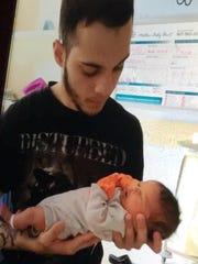 Esteban Santiago in the hospital with his newborn son