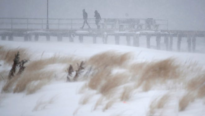 People walk on a small pier as snow covers the sand dunes during a snowstorm that hit the Jersey Shore on Thursday. Areas right along the coast got the heaviest snowfall in the mid-Atlantic during the massive winter storm that swept from the Carolinas to Maine.