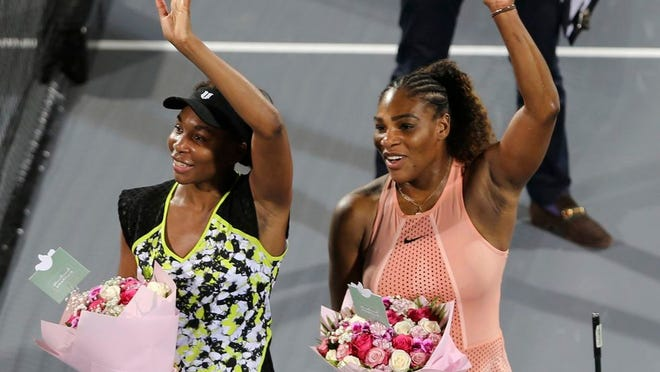 Dec. 27, 2018, Venus Williams, left, celebrates winning against her sister Serena, right, after a match on the opening day of the Mubadala World Tennis Championship in Abu Dhabi, United Arab Emirates. Serena Williams is looking forward to getting back to competing on a tennis court when the coronavirus pandemic permits it. Her older sister, Venus, is looking forward to hanging out at a rooftop bar. Two of the most famous and successful siblings in the history of sports shared those thoughts and more Tuesday, May 12, 2020, after doing some yoga together during an online session that offered workout tips and some laughs.