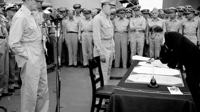 FILE - In this Sept. 2, 1945, file photo, U.S. General Douglas MacArthur, left, watches as the foreign minister Manoru Shigemitsu of Japan signs the surrender document aboard the USS Missouri on Tokyo Bay. Lt. General Richard K. Sutherland, center, witnesses the ceremony marking the end of World War II with other American and British officers in background. Wednesday, Sept. 2, 2020, is the 75th anniversary of the formal Sept. 2, 1945, surrender of Japan to the United States, when the two sides signed documents officially ending years of bloody fighting in a ceremony aboard the USS Missouri in the Tokyo Bay, with an armada of American warships and planes hovering nearby.