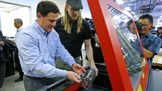 Michael Bortfeld shows shows Gov. Doug Ducey  how a C02 laser etches glass after Ducey signed HB2591  in April  2015 at TechShop in the ASU Chandler Innovation Center.  The measure was designed to broaden the way crowd-sourcing can be used to help fund start-up businesses