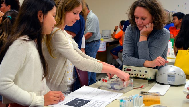 DNA Learning Center Assistant Director Amanda McBrien looks on as World of Enzymes camp participants set up apparatus for gel electrophoresis in Cold Spring Harbor, N.Y.
