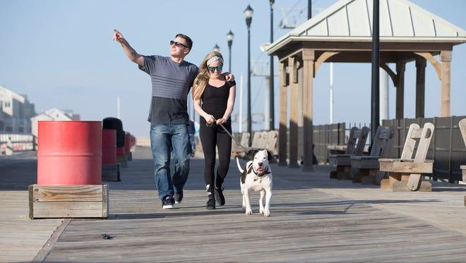 Eric Muraczewski and Torrie Stevenson, both of Toms River walk Simon. Warm weather on the boardwalk.Seaside Heights, NJFriday, February 24, 2017.@dhoodhood