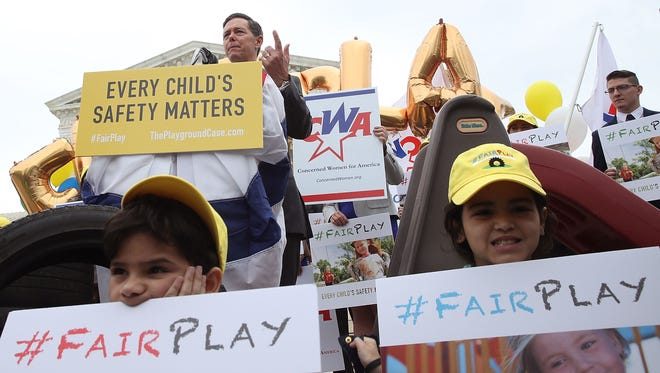 Defenders of religious freedom demonstrate outside the Supreme Court Wednesday during oral argument in a case involving a church's exclusion from a state grant program for playground safety.