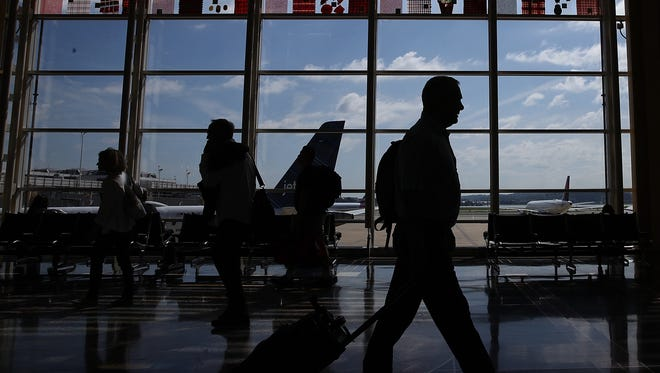 Travelers walk to their gates in the concourse of Reagan National Airport in advance of the Fourth of July holiday on June 29, 2018 in Washington, DC.
