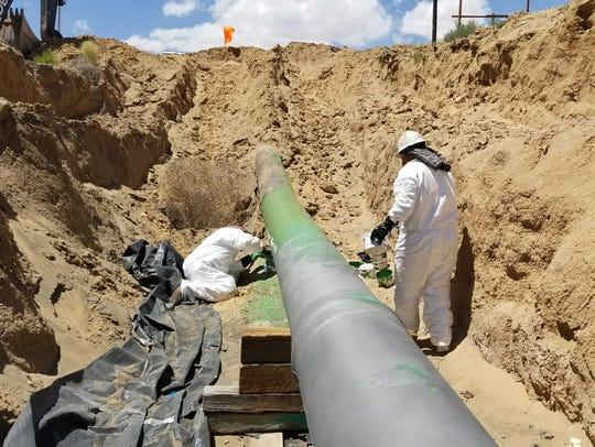 Navajo Nation Oil and Gas Company employees apply a