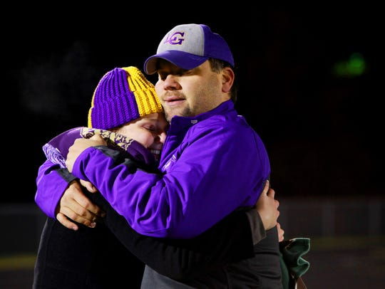 Amy Clark hugs her husband, Corey, who is an assistant