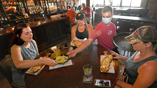 Friends, from left, Jenna Bailey, 23, Alicia Buterbaugh, 29, and Amanda Spellman, 31, are served lunch on June 26 by Joe Campbell at U Pick 6 Harbor House in Harborcreek Township. Gov. Tom Wolf announced Tuesday that restaurants can expand to 50% indoor capacity beginning Sept. 21.