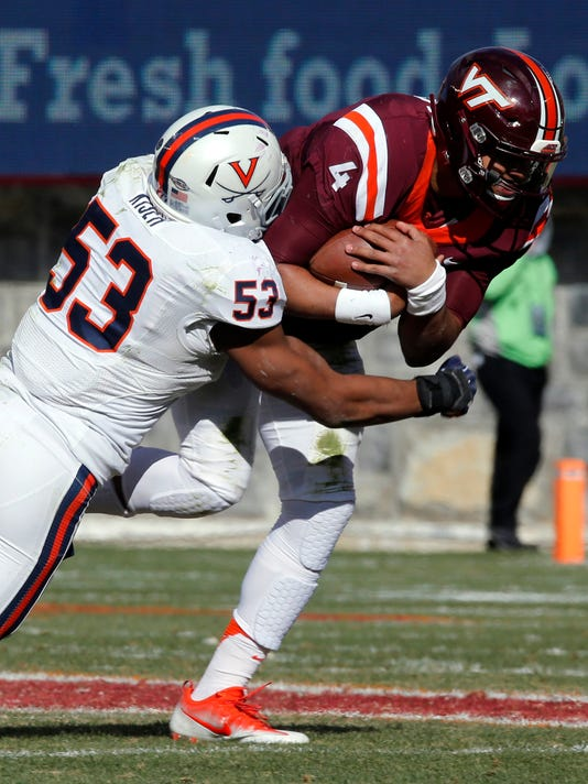 FILE - In this Nov. 26, 2016, file photo, Virginia linebacker Micah Kiser (53) wraps up Virginia Tech quarterback Jerod Evans (4) during the first half of an NCAA college football game in Blacksburg, Va. Kiser is the anchor for a Cavaliers defense heading south to play North Carolina. (AP Photo/Steve Helber, File)