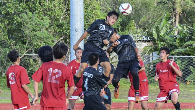 """Aaron """"A-A-Ron"""" Castro of the Simon Sanchez Sharks elevates above the crowd in an Independent Interscholastic Athletic Association of Guam Boys' Soccer League match against the St. John's Knights at Okkodo field on Nov. 5."""