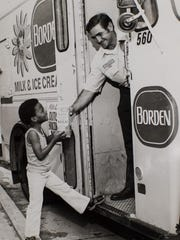 An undated photograph shows a milkman delivering a carton to a child as part of the Milk Fund program in Lafayette.