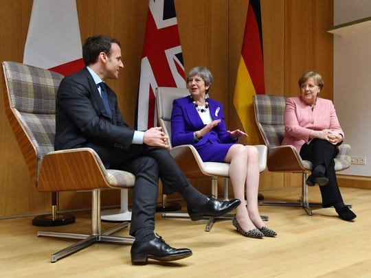 French President Emmanuel Macron, British Prime Minister Theresa May and German Chancellor Angela Merkel meet on the sidelines of a European Union leaders summit in Brussels on March 22.