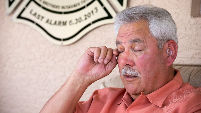 Former Prescott Fire Chief Dan Fraijo wipes his eyes as he recounts the tragedy of the Yarnell Hill Fire as he sits below a metal plaque given to him by the family of Granite Mountain Hotshot Travis Turbyfill at his home in Prescott on Monday, June 2, 2014.
