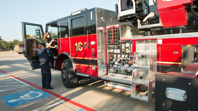 Fire Chief Andres Rosales (left) and Mayor Connie Schroeder tour the fire department's new ladder truck before the fire truck was taken on a stroll through town on Tuesday for National Night Out.