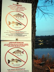 Signs along the edge of Pompton Lake warn people not